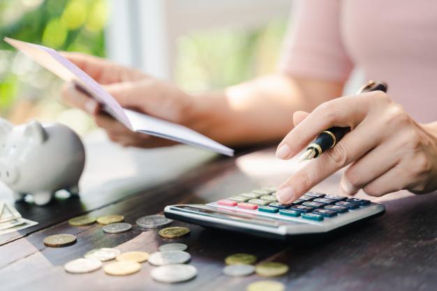persona usando calculadora con libreta bancaria
