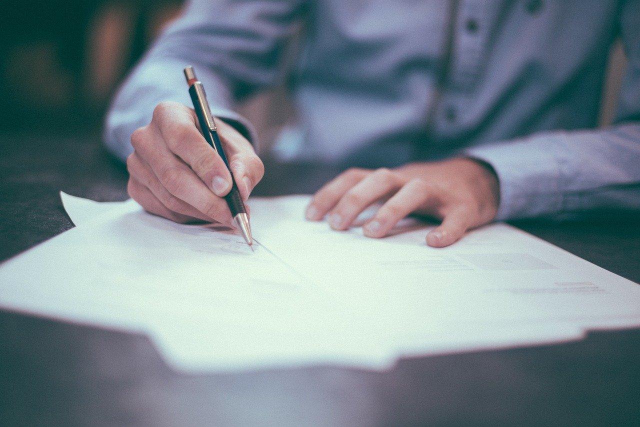 Persona firmando un documento