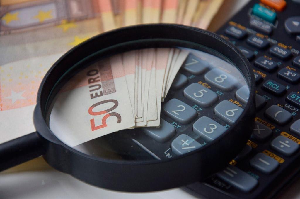 Una lupa sobre una calculadora y billetes
